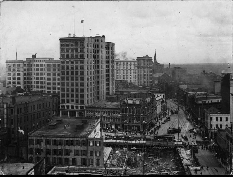 "Aerial view of Five Points, showing the construction of the Fourth National Bank building, Atlanta, Georgia, 1904. Original photo mount has newspaper caption attached to verso: ""Above -- Five Points many years ago. This picture, looking north on Peachtree, shows excavations being dug for the Fourth National Bank building, since rebuilt as the First National Bank building. Across the street is the site of the present William Oliver building."" The added paper mount has two captions: ""Five Points when work started on the First National Bank Building"" and ""The excavation for the First [crossed out and ""Fourth"" penciled in] National Bank building at Five Points. The old structure on the opposite corner was later replaced by the William-Oliver building. As the tall skyline shows, Atlanta already had quite a number of skyscrapers."" Paper mount dated ""1904."" This image was later printed as a postcard."